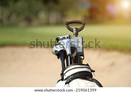 golf bag and professional golf gear on the golf course at sunset - stock photo