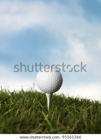 Golf ball on a peg in the grass - stock photo