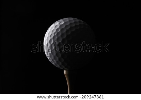 golf ball on a tee, in dramatic black and white - stock photo