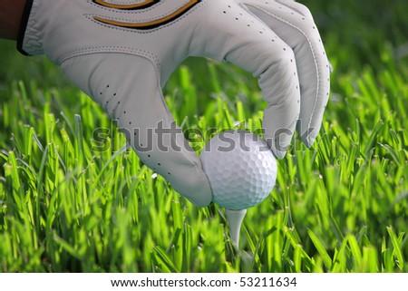 golf glove with ball on tee - stock photo