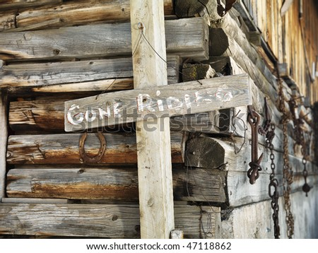 'GONE RIDING' sign against an old weathered, wooden stable. Horizontal shot.