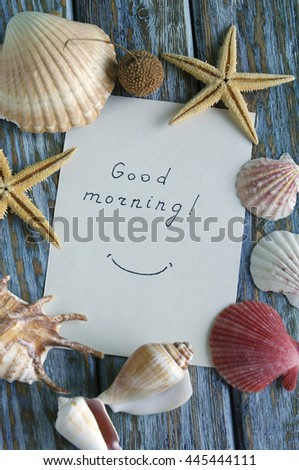 """Good morning"" is written on small paper with seashells"