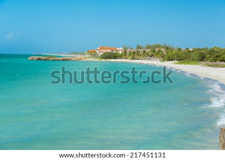 Gorgeous amazing view of tranquil emerald ocean, white sand beach with stone cliffs and tropical palm tree garden against blue clear sky - stock photo