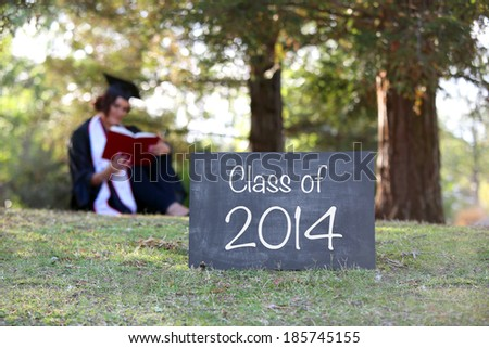 2014 graduate reading in cap and gown - shallow depth of field - stock photo