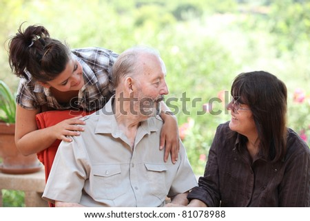 granddaughter and daughter visiting happy smiling grandfather - stock photo