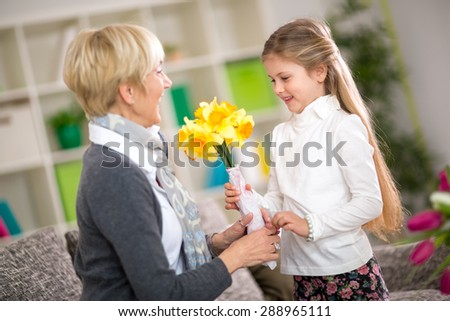 Granddaughter bringing yellow flowers to her grandmother, grandmother day - stock photo
