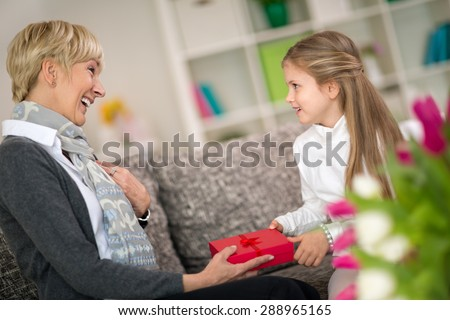 Granddaughter giving gift to her grandmother, surprise for sweetheart grandma - stock photo