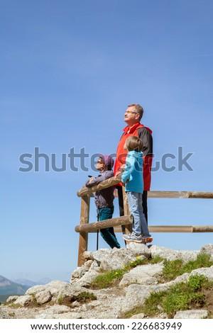 grandfather and two grandchildren admire the scenery on the cliff - stock photo