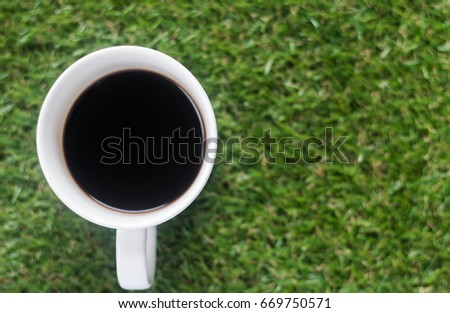 grass background There is a white coffee mug placed on the grass in the glass with black coffee.
