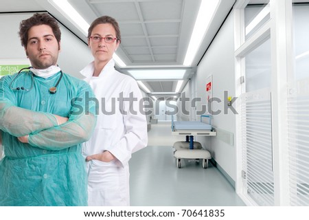 Grave looking hospital personnel standing by a corridor - stock photo