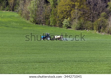 green agricultural field with cereals, which are processed by a tractor - stock photo