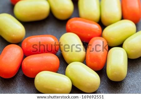 Green and orange candy on dark background. - stock photo