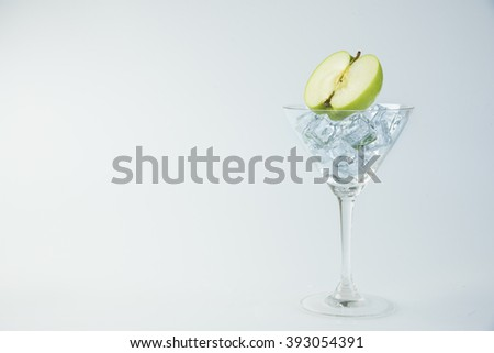Green apple cocktail glass on white background.