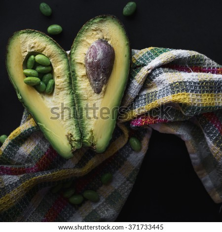 green avocado fruit on a dark background with soy beans called edamame - stock photo