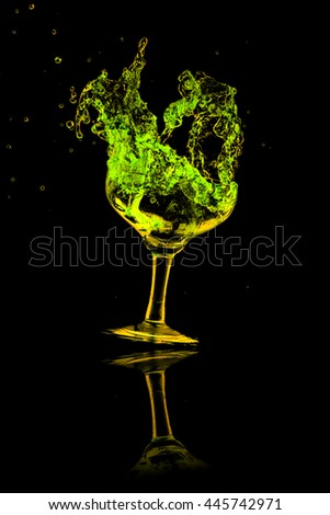 green cocktail splash out of glass on black background. - stock photo