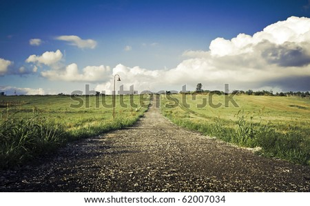 Green field Landscape with country road - stock photo