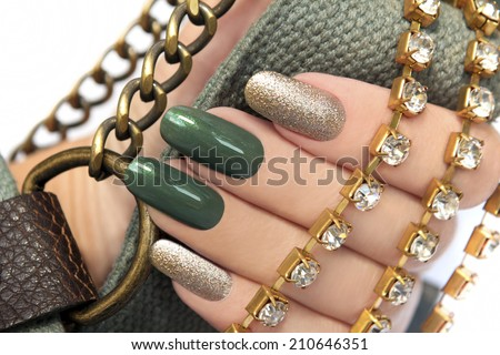 Green manicure with a brilliant gold lacquer on oval shaped nails. - stock photo