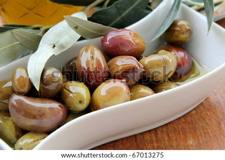 green Olives and Olive Oil on a wooden table - stock photo