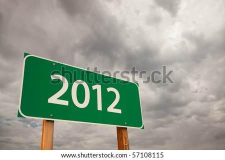 2012 Green Road Sign with Dramatic Storm Clouds and Sky. - stock photo