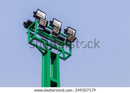 green spotlights pillar on blue sky background - stock photo