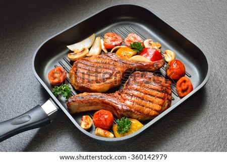 Grilled pork chops and vegetables on the grill pan   - stock photo