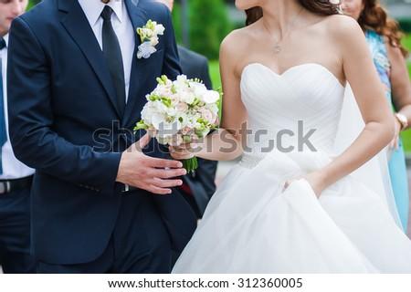 Groom hugs bride. Big wedding bouquet. - stock photo
