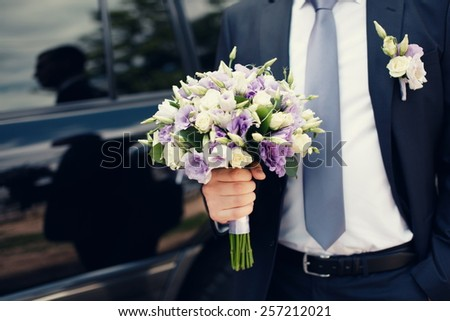 Groom with wedding bouquet close up  - stock photo