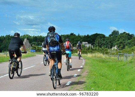 group of cyclists going on the road in the countryside - stock photo