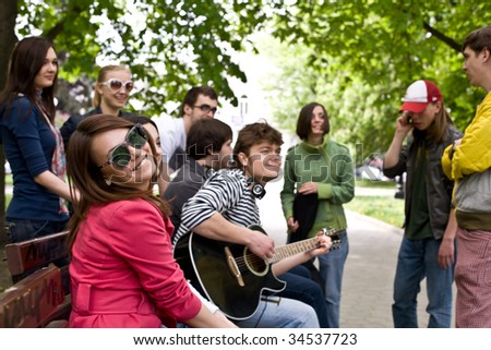 Group of people on city in park. Music. - stock photo