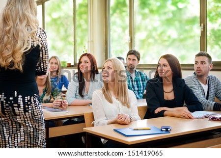 Group of students listening to teacher in classroom