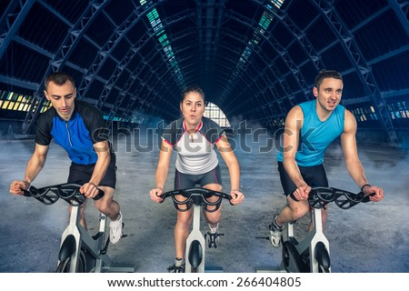 group of three people exercise on bike, spinning class, - stock photo
