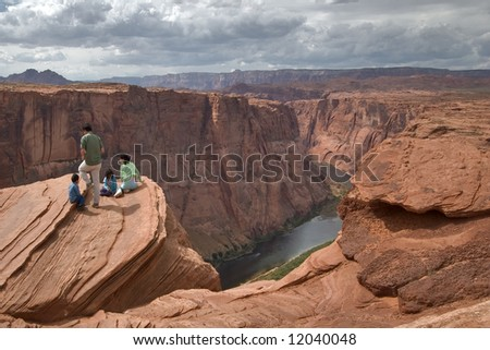 Group of tourists on edge of a deep canyon Horseshoe in state of Utah in the USA - stock photo