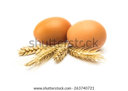 group of two brown eggs with grain ears isolated on white - stock photo