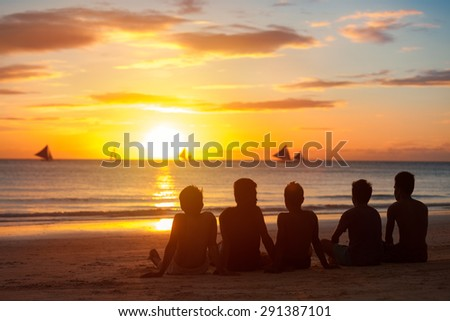 group of young  people, friends, team sitting  together on beach, sunset sky - stock photo