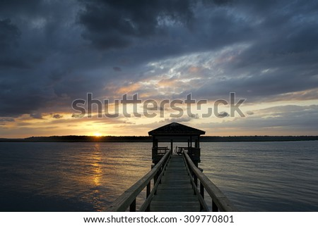 """""""Growing Dark On the Dock"""" Another dramatic Lowcountry sunset over the Colleton River tidal estuary near Hilton Head Island, SC. - stock photo"""