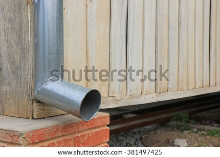 gutter metal rain drain pipe on the wall - stock photo