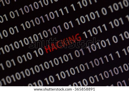 'Hacking' word in the middle of the computer screen surrounded by numbers zero and one. Image is taken in a small angle.