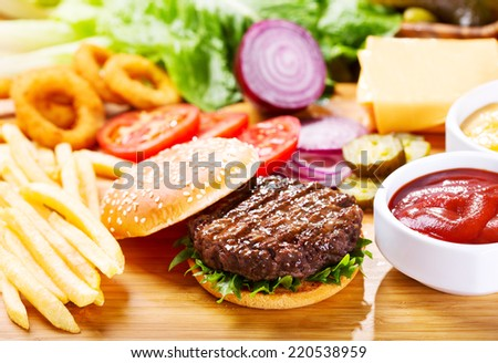 hamburger with fresh vegetables on wooden table - stock photo