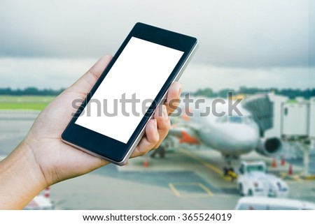 Hand Checking-In For A Flight Using Cellphone, hand holding mobile phone with flight mode in the airplane, phone in the hand with a blank screen and blurred a plane in the background   - stock photo