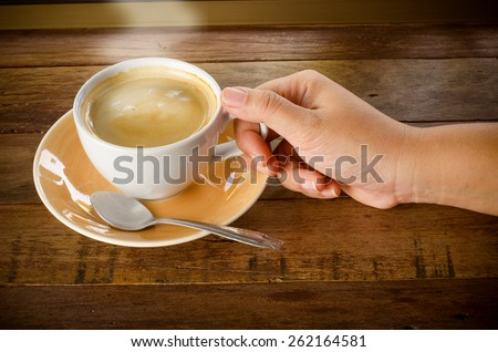 hand holding cup of coffee on wooden table. - stock photo