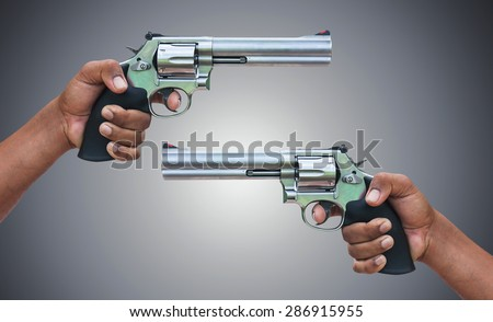 hand holding  revolvers on gray background - stock photo
