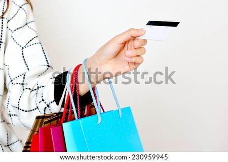 hand holding shopping bags and one credit cards - stock photo