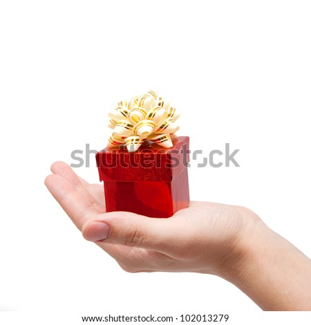 hand is holding single red gift box with silver-beige ribbon. Isolated on white background with clipping path - stock photo