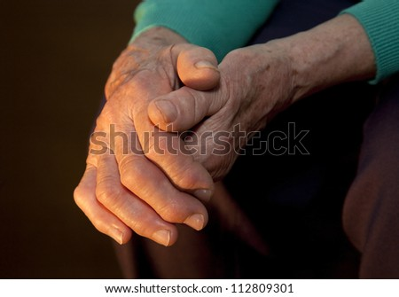 hand of old woman in the dark and light
