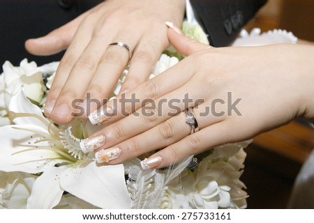 Hand of the unveiling of the bride and groom of gorgeous wedding ring