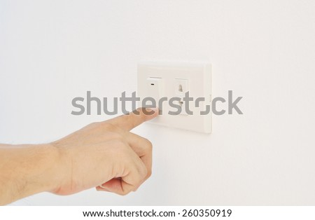 Hand pressing electronic-light switch - stock photo