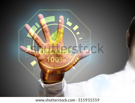hand pushing Organic on a touch screen interface - stock photo