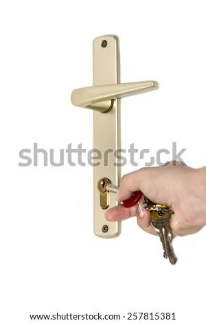 Hand putting house key into front door lock - stock photo