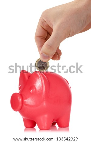 Hand putting one Euro coin into the piggy bank - stock photo