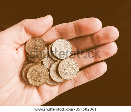 Hand with British Pound coins currency of the United Kingdom vintage - stock photo